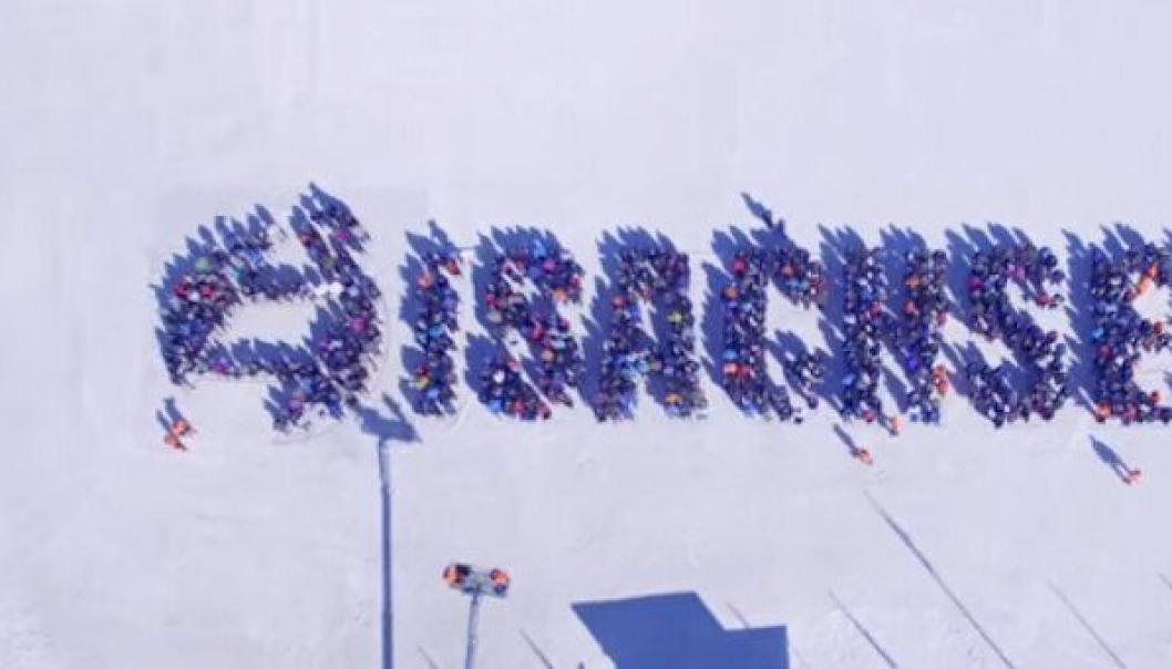 Bilde fra jubileumsvideoen «Vi gjør det» som ble filmet i løpet av helgen. Ansatte med følge danner logo og firmanavnet, filmet med drone. Se videoen lenge ned i saken.