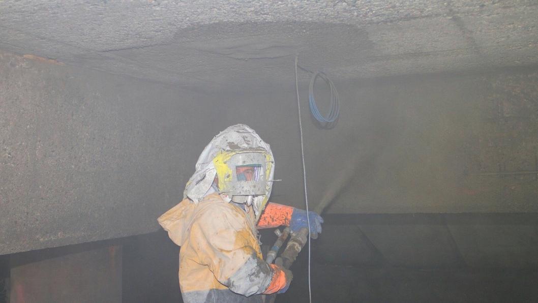 Under Hurtigrutekaia i Kirkenes er Marek Koziol i Consolvo i full sving med å tørrsprøyte med betong.
