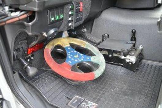 Ved/på gulvet ved førersetet finnes alle nødvendige styreinnretninger for å kunne styre lastebilen med føtter/tær.