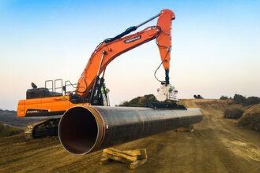 SEIRET: Med kort stikke, store krefter og bredbent understell vant 55-tonneren fra Doosan konkurransen om håndtering med vakuumløfter og legging av de 18 meter stålrørene.
