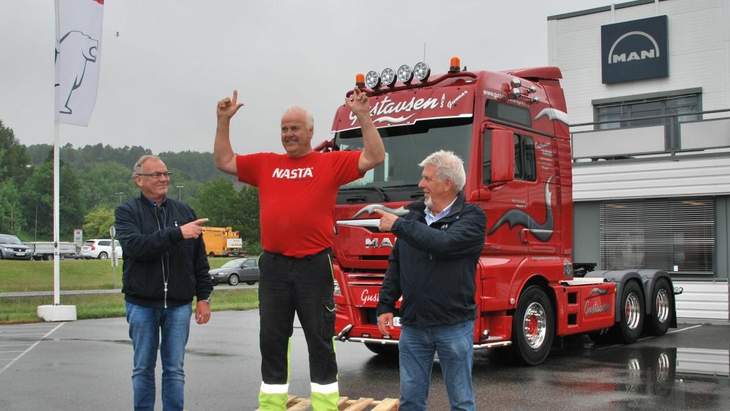 Hovedpersonene samlet på pallen foran den nye lastebilen. Sjåfør Gunnar Eftedal er flankert av daglig leder Ian Karl Gustavsen (t.v.) og MAN-selger John Hunsrød.