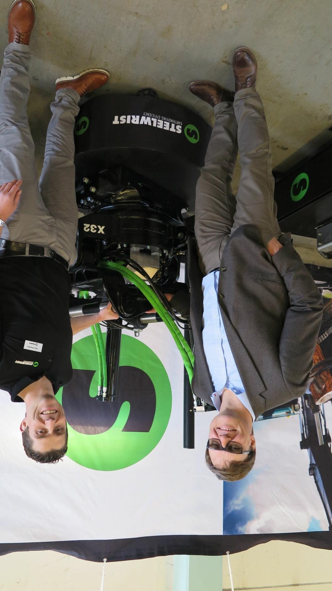 En stolt og lettet Steelwrist-sjef Stefan Stockhaus (t.v.) og Norges-leder Stian Brække foran tiltrotatoren X32 som kom allerede i 2014, men nå har fått fast OQ-topp. Redskapet har lav byggehøyde, vekten er lav, men styrken er økt.