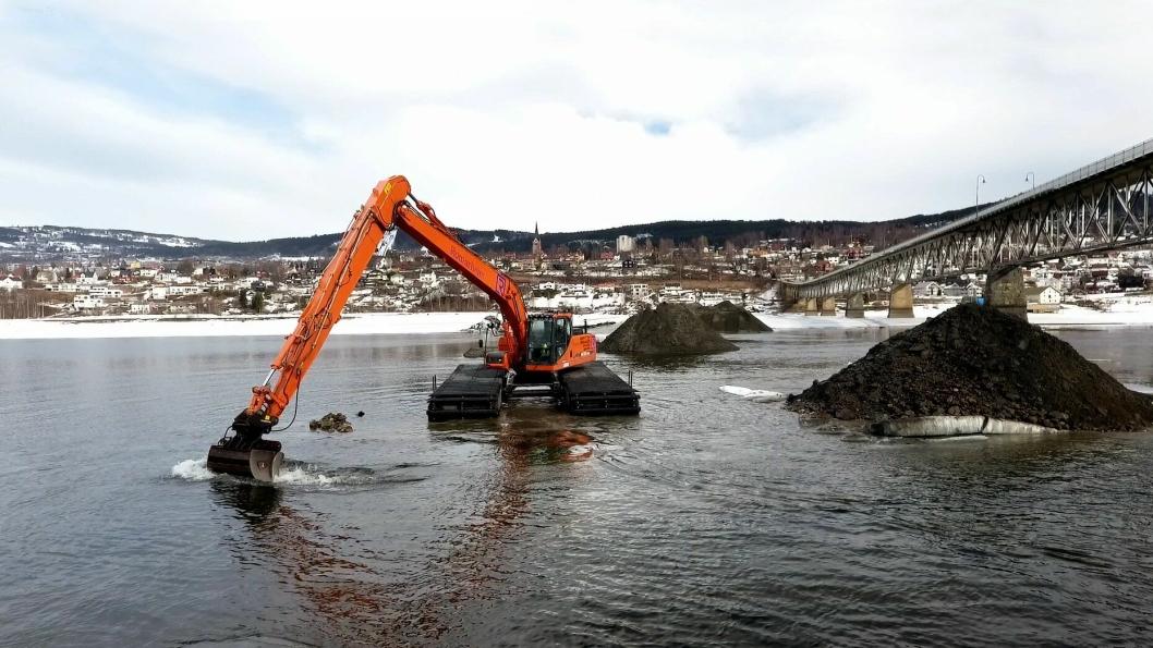 Waterking graver grøft for nye vann- og avløpsledninger like ved Vingnesbrua mellom sentrumssiden i Lillehammer og Vignes. Lillehammer skimtes i bakgrunnen.
