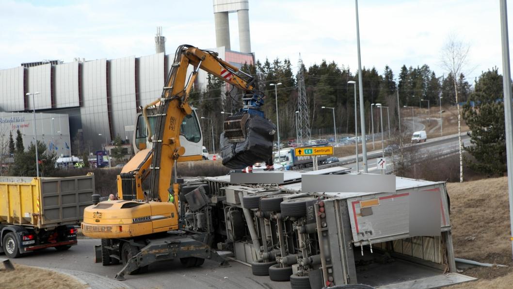 Den veltede tralla ble tømt med en materialhåndterer. Avfallsforbrenningsanlegget, Klemetsrudanlegget AS, i bakgrunnen.