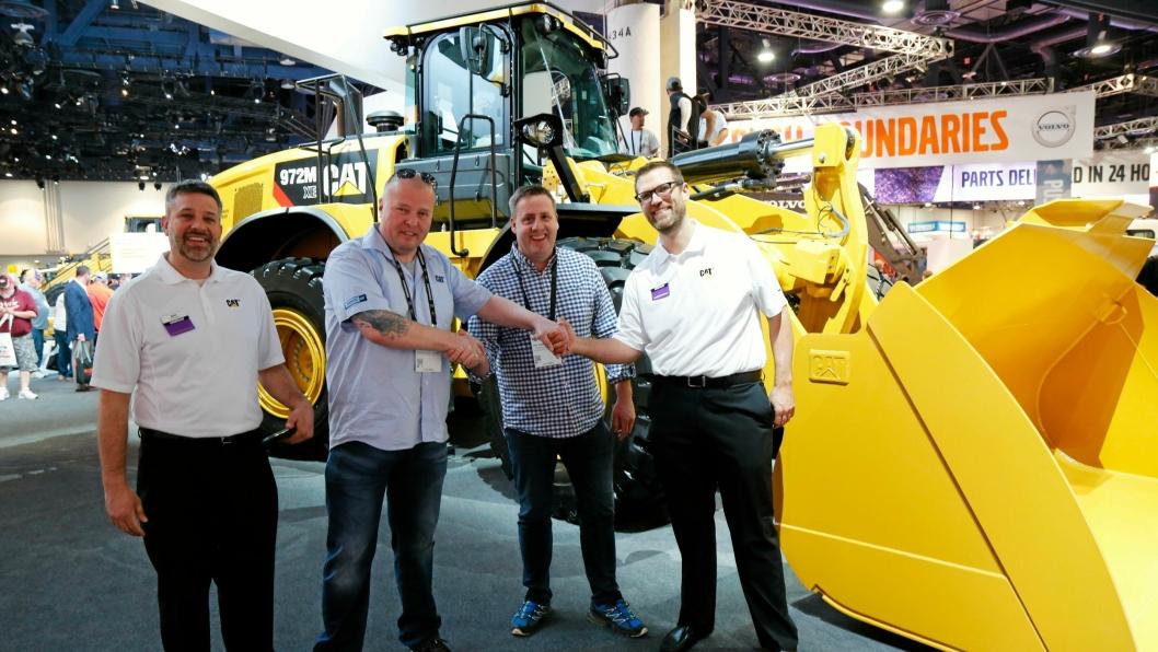 Det ble kjøp av en Cat 966M XE-hjullaster. Her er det «shake hands» på Cat-standen. Fra venstre: Mike Spielman (Caterpillar), Rune Madsen (Roald Madsen AS), Per Gunnar Hansen (Pon Equipment) og Ben Schmuck (Caterpillar).
