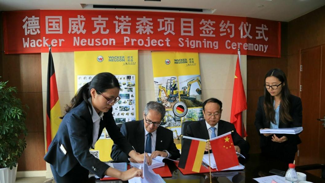 SIGNERING: Wacker Neusons toppsjef, Cem Peksaglam (t.v.) og Zhou Diming, utviklingsdirektør i Pinghu-distriktet, signerer avtalen som klargjør for å sette spaden i jorda.