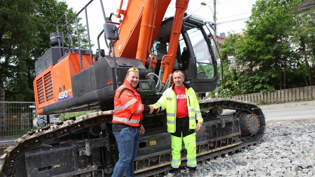 Selger Sjur Wethal i Nasta AS (t.v.) gratulerer maskinfører Tor Hansen med ny gravemaskin - en Hitachi ZX 490LCH - ved overleveringen på Kolbotn 20. juni 2016.