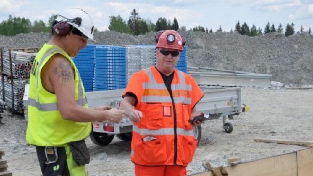 HMS-rådgiver Stig Harry Andersson (t.h.) i Statens vegvesen kontrollerer ID-kortet til en arbeider på E134 Damåsen-Saggrenda prosjektet.