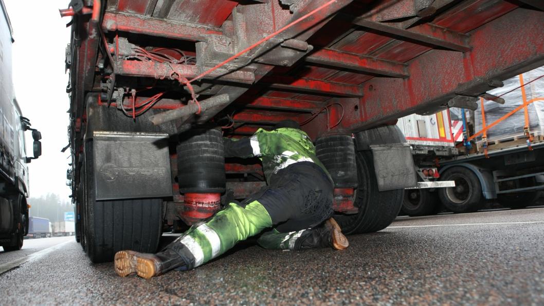 Bilde fra mars 2014 av en tralle med bremsefeil som ble stoppet på Taraldrud kontrollstasjon i Akershus. Sjåføren kjørte og leverte varene i Oslo tross bruksforbud. Personen på bildet er en tilkalt mekaniker.