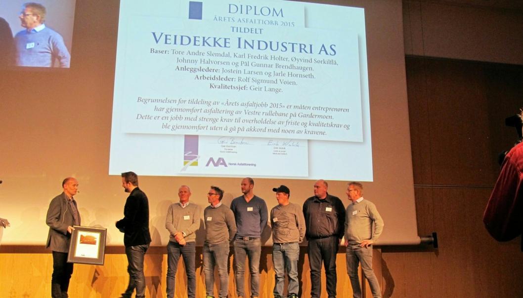 ASFALT-HELTENE: Formann Geir Berntsen i Norsk Asfaltforening hedrer de av Veidekke-laget som var tilstede på konferansen.
