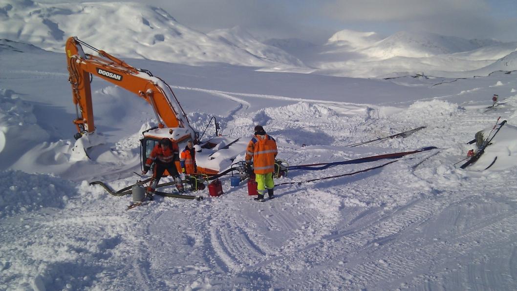 Mannskapet er i gang med å dra opp 32-tonneren fra snømassene som dekket store deler av maskinen.