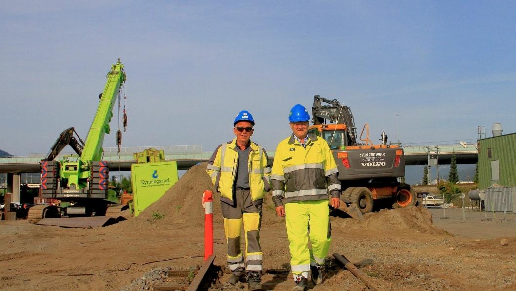 Prosjektleder Kjell Otnæs (t.h.) og byggeleder Jan Nyman i Jernbaneverket ruslende på de gamle skinnene på Holmen. Arbeidene med nye kulverten er i gang i bakgrunnen.