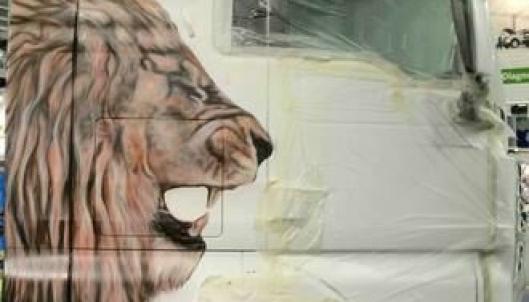 """Marete Lund Bakke er i ferd med å skape en """"levende"""" løve på siden av en MAN."""