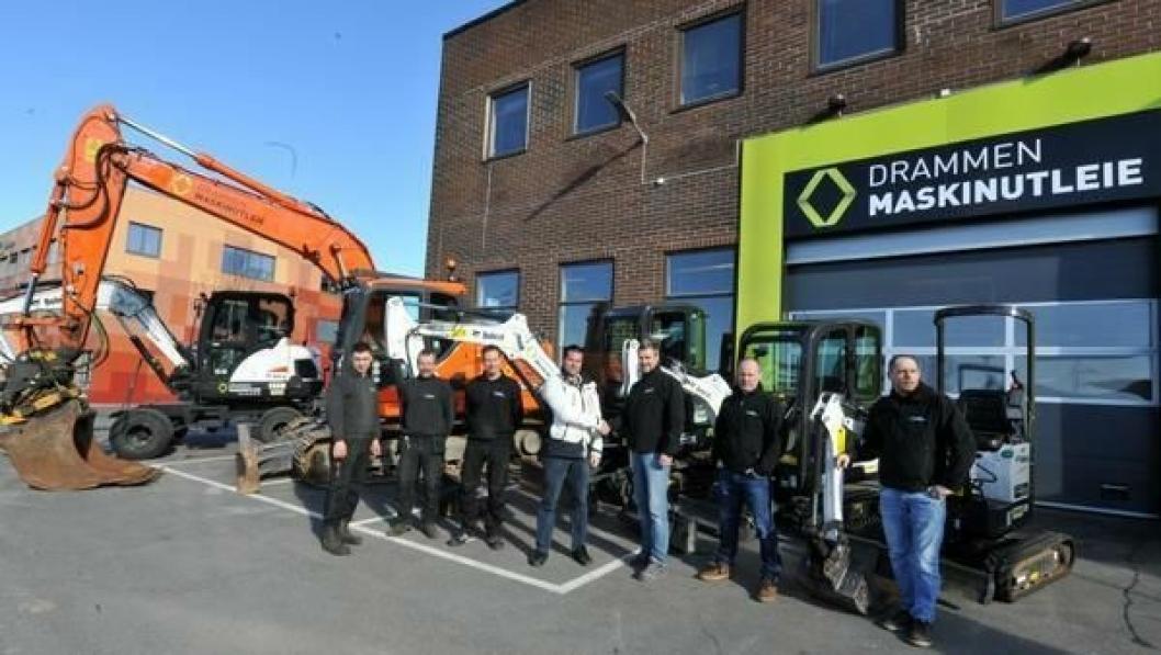 Oddvard Lien fra Drammen Maskinutleie tar Rosendal Maskin-selger Magne Reiersrud i hånda i nærvær av flere ansatte i utleieselskapet.