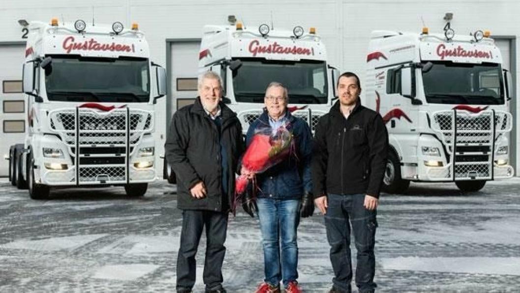 Daglig leder Ian Gustavsen (i midten) og Driftsleder Aslak Gustavsen (til høyre i bildet) får overrakt blomster av selger John Hunsrød hos MAN i Larvik.
