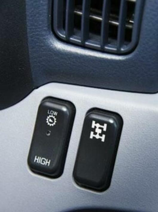Med disse bryterne og clutchpedalen kobler man inn forhjulsdriften og lav utveksling i overføringsgirkassen.