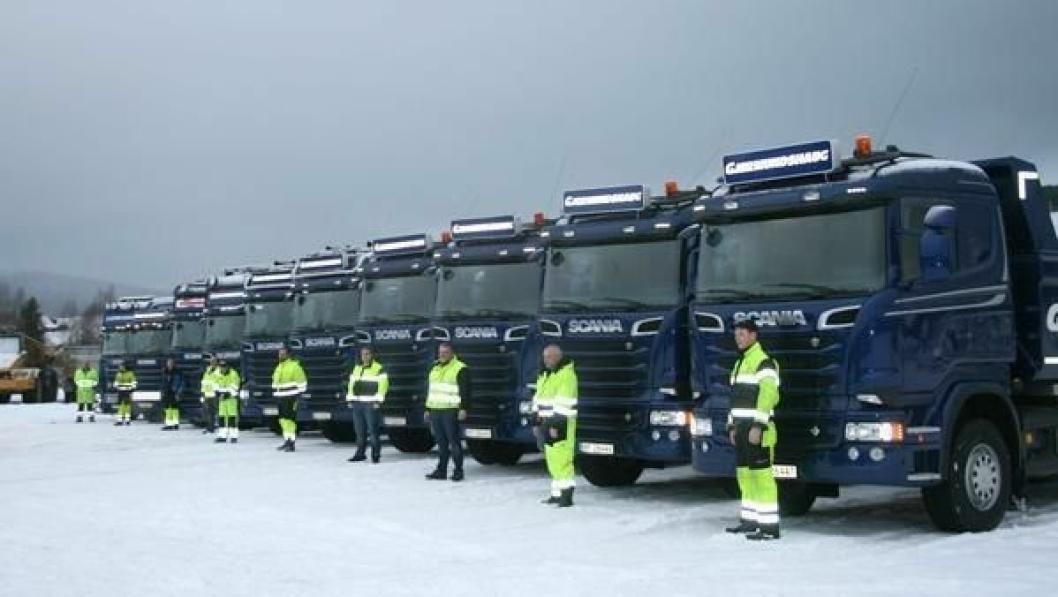 Sjåfører og biler på rekke og rad hos Gjermundshaug. De nyeste bilene står parkert nærmest kamera.