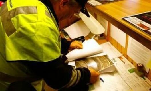 Avdelingsingeniør Aage Kristiansen i Statens vegvesen ser over bilder av bremseskiver med sprekk.