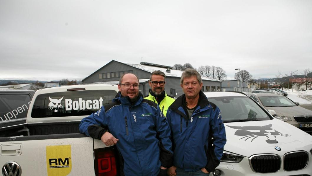 NYTT AGENTUR: De første maskinene kommer til Anleggsgruppens hovedkvarter i Lier i januar neste år, men firmabilene er allerede dekorert med Bobcat-logoer. Fra venstre er Paul Håkon Endresen, Magne Reiersrud og Per Gunnar Holmgren.