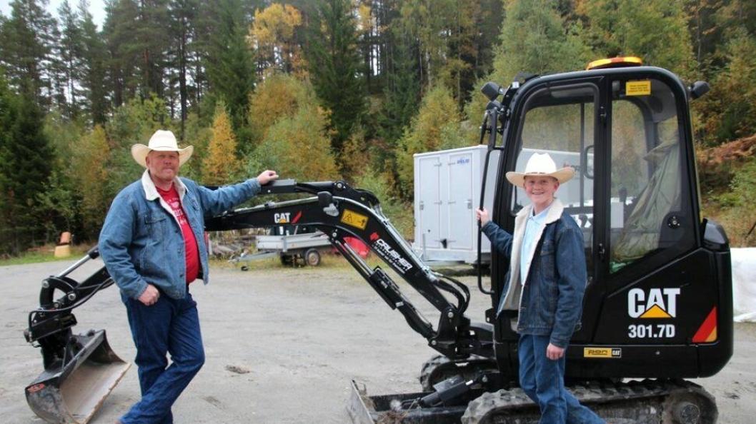 Christoffer og pappa Lloyd Sundstøl viser konfirmasjonsgaven, en Cat 301.7D. Foto: Gyril Sundstøl