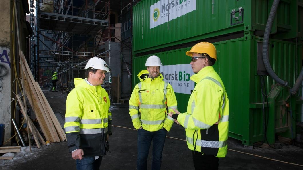 Salgs- og markedssjef i Utleiesenteret, Morten Dahl (t.v.), daglig leder i Norsk Bio, Henrik Kjæreng og anleggsleder hos JM Entreprenør AS, Thomas Rødseth, er enige om at det miljøvennlige fyringsanlegget i bakgrunnen er fremtiden med tanke på å redusere utslippene fra norske byggeplasser. Anlegget, som har trepellets som ernergikilde, er nå i drift i «Hollenderkvartalet» i Schweigaardsgate 40-46 i Oslo.