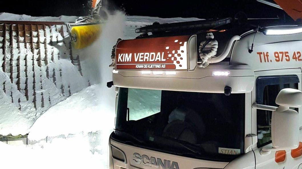 Kranbil fra Kim Verdal Kran og Kjetting AS i aksjon med å renske et tak for snø med feiemaskin på kran.