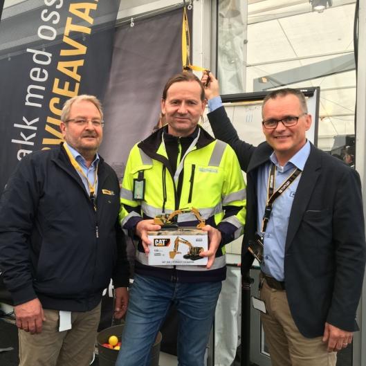 BJELLEKLANG: Pons adm. direktør Erik Sollerud (høyre) ringer i bjella på standen til Pon etter at Lars Firing (midten) har bestilt to Cat 323F Z Line av Pon Equipment og selger Tord Pettersen.