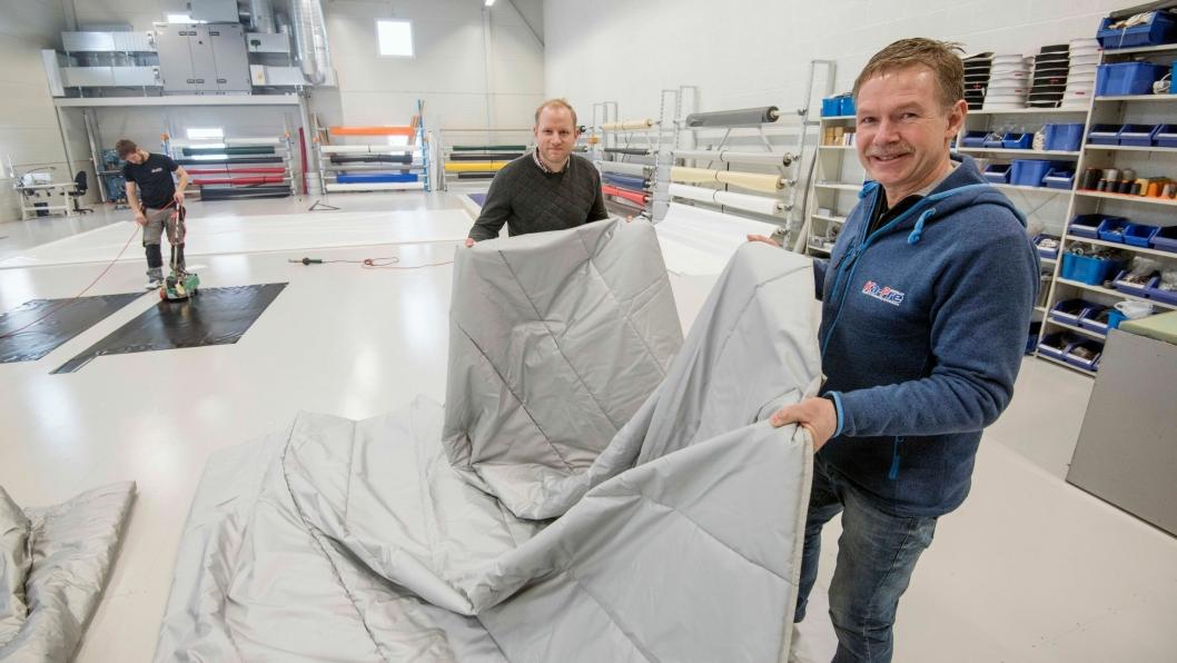 VARME: Med denne duken som Håvard Saastad (til venstre) og Bjørn Gunnar Thalerud bretter, holder på temperaturen i asfalten seg mye lenger.