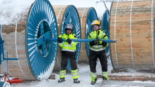 TUNGE TAK: To mann tar i for å frigjøre den nesten ni tonn tunge trommelen fra sleden. Her er Mikkel Sokki (t.v.) og Paul Inge Thomassen.