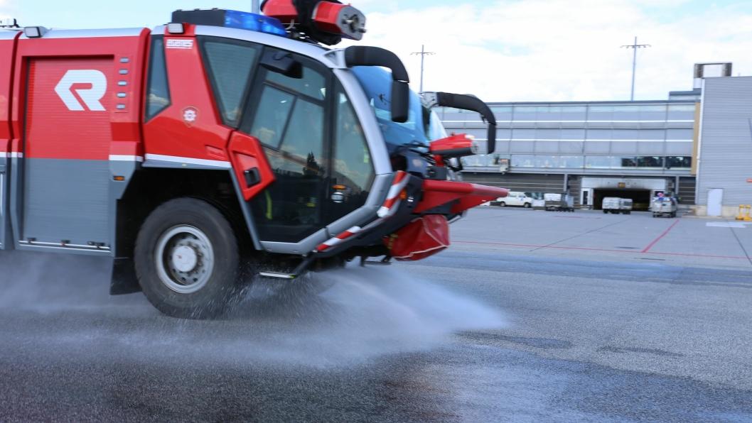 Brannbil vanner varm asfalt på Oslo Lufthavn. Bildet er fra vanning sommeren 2014, på samme måte som det gjøres denne sommeren.