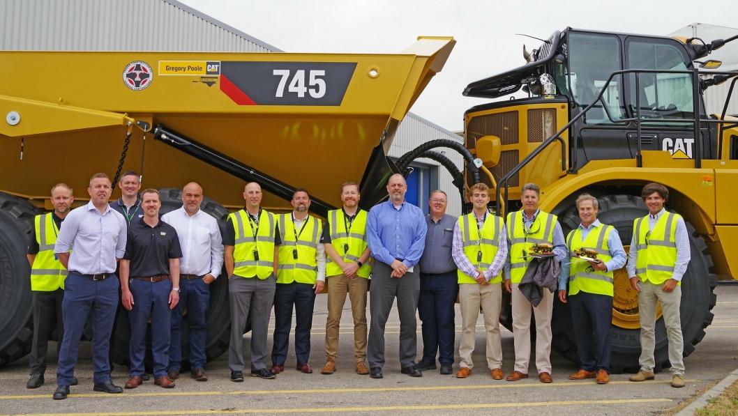 Representanter for Caterpillar, forhandler Gregory Poole og kunde Trader Construction Company ved overleveringen av rammestyrt Cat nummer 50.000 produsert ved fabrikken i Peterlee i Storbritannia.