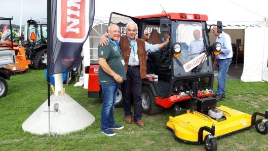 Geir Enersen (t.v.), Lier Traktor AS og Nimos-direktør Nico Drost ved den nye redskapsbæreren som ble vist på den danske utstillingen «Maskiner under broen».
