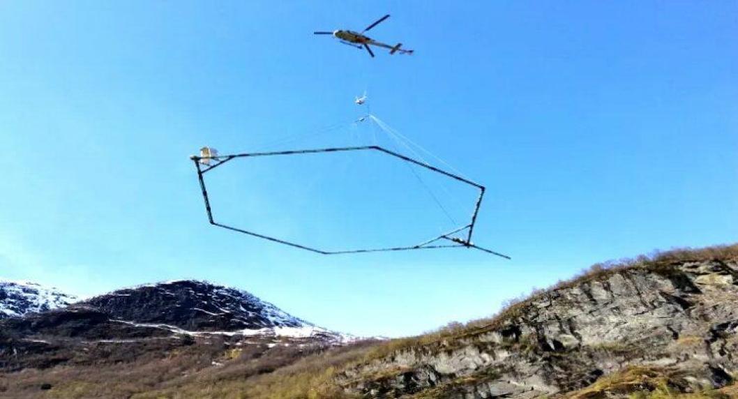 Antennen som registrerer grunnforholdene henger under helikopteret som kjører over områdene som ønskes undersøkt.