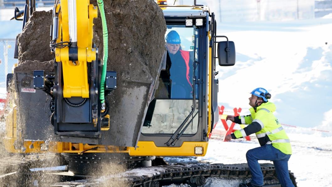 Statsminister Erna Solberg gjennomfører første «spadetak» med gravemaskin, til det som blir Norges største universitetsbygg.