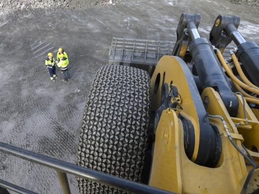 SMÅGUTTER: De tre karene som står på bakken og prater foran for det ene forhjulet blir som smågutter å regne fra toppen av maskinen.