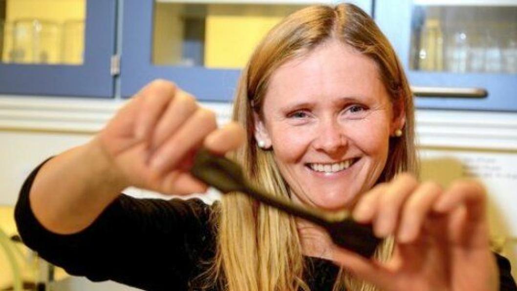 Seksjonssjef Wenche Hovin viser en strekktest av bitumen ved Vegvesenets laboratorium, Sentrallaboratoriet i Trondheim. Testen viser hvor elastisk prøven er.