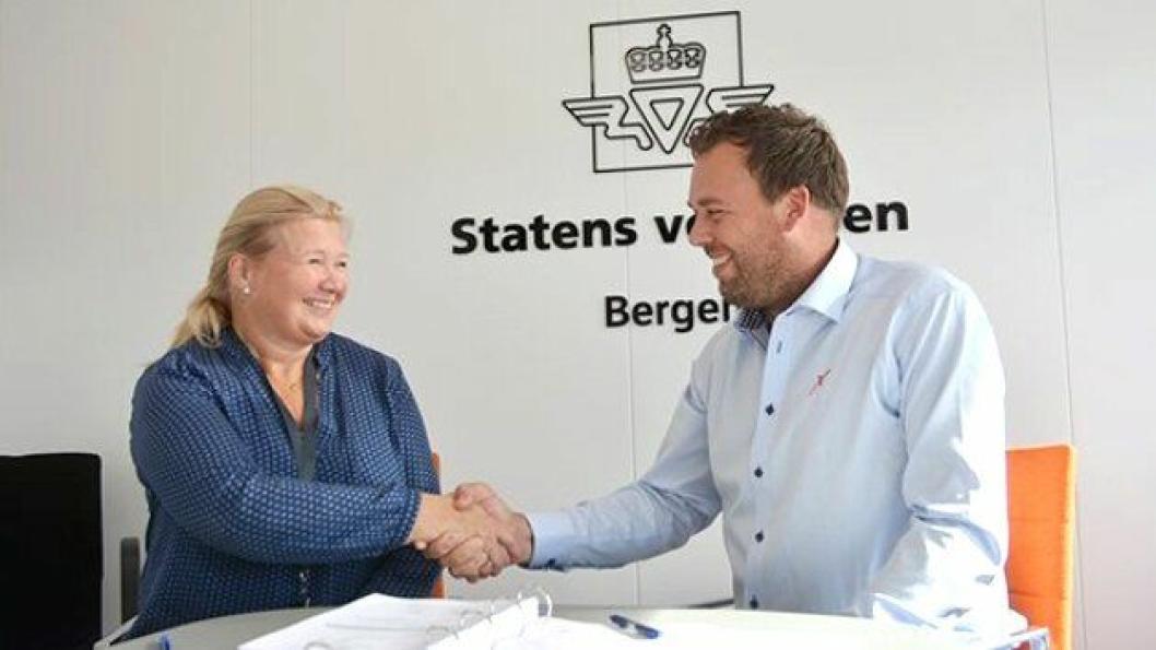 Avd.dir. Grethe Vikane i Statens vegvesen gratulerer daglig leder Knut Brusletto i Contexo AS med kontrakten.
