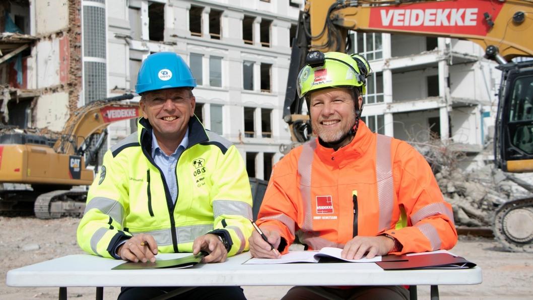 Konserndirektør boligutvikling Arne Baumann i Obos (t.v.) og konsernsjef Jimmy Bengtsson i Veidekke signerte M17-kontrakt på rivetomta.