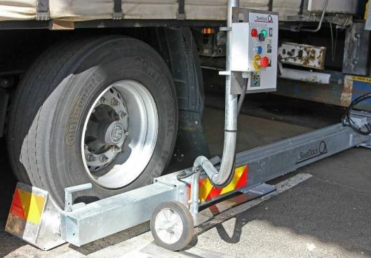 Lastebilens ene hjul låses fast før lossing kan startes. SweDocks lastsikringsutstyr er enkle å montere som sikrer lastingen og lossingen av lastebiler ved rampene.