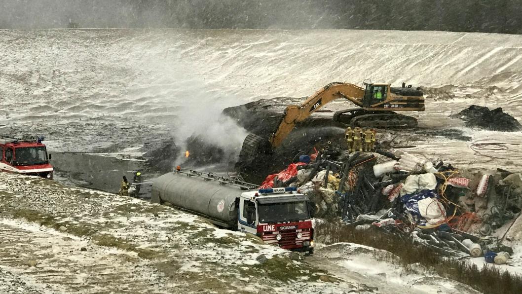 Brannen i avfallsdeponiet blusser stadig opp. En gravemaskin snur massene slik at brannmannskapene kommer til brannen.
