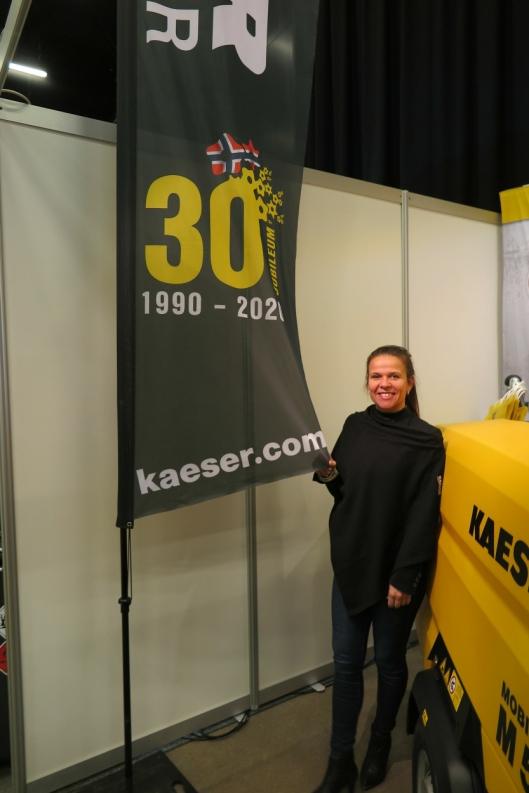 Markedskoordinator hos Kaeser Kompressorer AS, Cathrine Brich, med jubileumsfane på Arctic Entrepreneur 2020 på Gardermoen.
