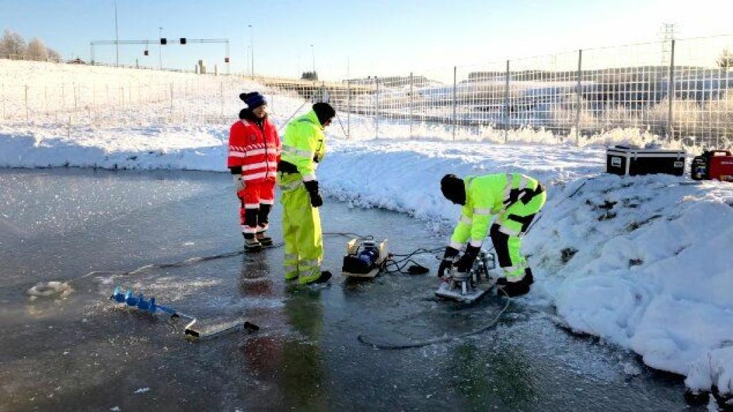 Forskere tar prøver fra Fossbekken rensebasseng som samler opp veivann fra E18 i Spydeberg.