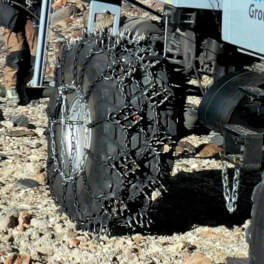 Kjettingene på bakhjulene på den ene Unimog-en fungerer dårlig på vei, men gir godt grep i det bratte terrenget med stein, grus, snø og is på fjellet Ojos del Salado i Chile.