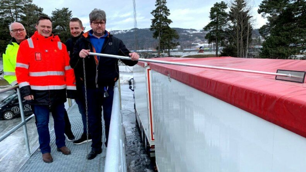 Her demonstrerer lastebilsjåfør Kjetil Markeng hvordan snø og is enkelt kan fjernes fra biltaket når han står på snøfjerningsrampen. Han er flankert av, fra venstre, leder NLF Innlandet, Guttorm Tysnes, avdelingsdirektør Drift og vedlikehold Øst, Cato Løkken, og styreleder NLF Innlandet, Arild Olsbakk.
