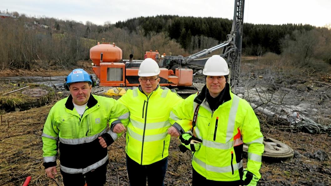Fra venstre: Samarbeidstrioen Alf Saur (NVE), Torstein Engen (YIT) og Gunnar Prøis (Nittedal kommune) med boreriggen og rasområdet mot Nitelva som bakgrunn.