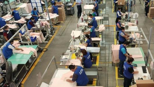 Ford-ansatte syr beskyttelsesfrakker av kollisjonsputemateriale.