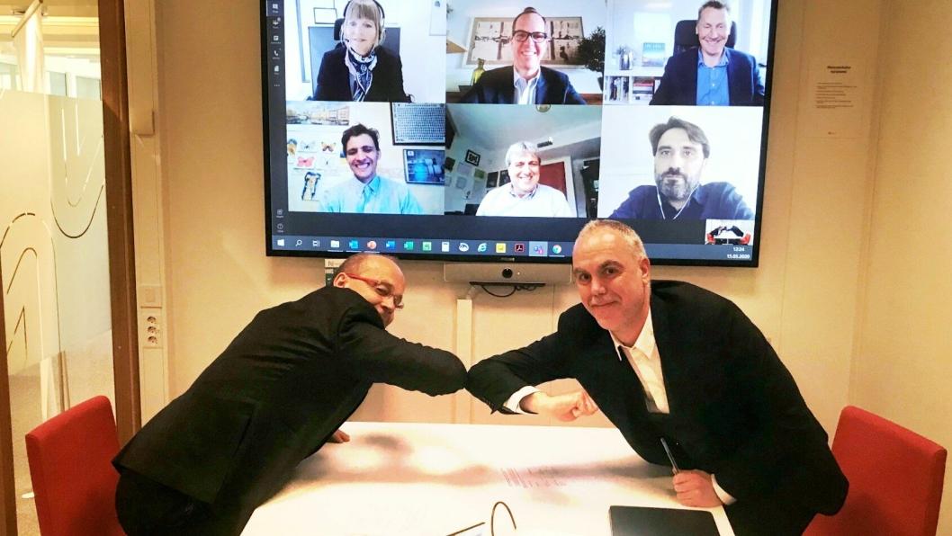 Digital signering med alternativt håndtrykk. F.v: Prosjektdirektør i Nye Veier, Johan Arnt Vatnan, og Pablo García Caramés, finansdirektør for Norge i Acciona. På skjermen ser vi flere fra ledelsen til de to selskapene: Anette Aanesland, administrerende direktør i Nye Veier er oppe til venstre i skjermen.