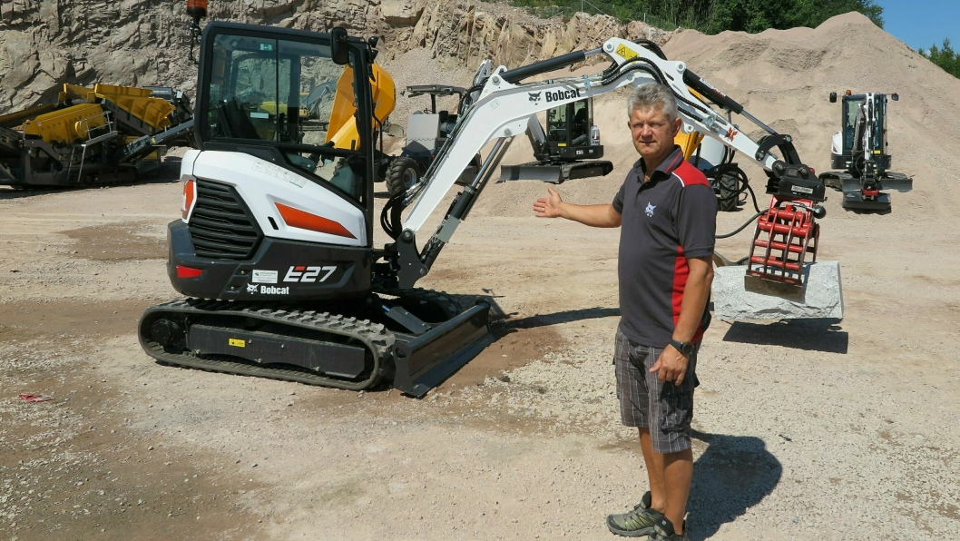 STOLT: Daglig leder Per Gunnar Holmgren med bestselgeren Bobcat E27 med en kraftig steinblokk i klypa og mindre maskiner som bakgrunn.