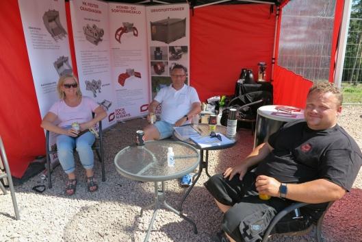 I SKYGGEN: Hanne Bjørnrud Johansen og Trond A. Rasmussen fra SG Finans hadde søkt skygge for brennhet sol i teltet til Stig Ove Kløvstad (t.h) fra Gjerstad.