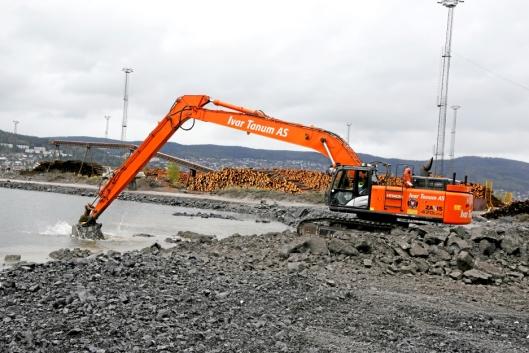 LANGARMET: Hitachi 470-graveren med 22 meters graveaggregat veier ca. 60 tonn. Maskinen løfter stein langt ut i vannet.